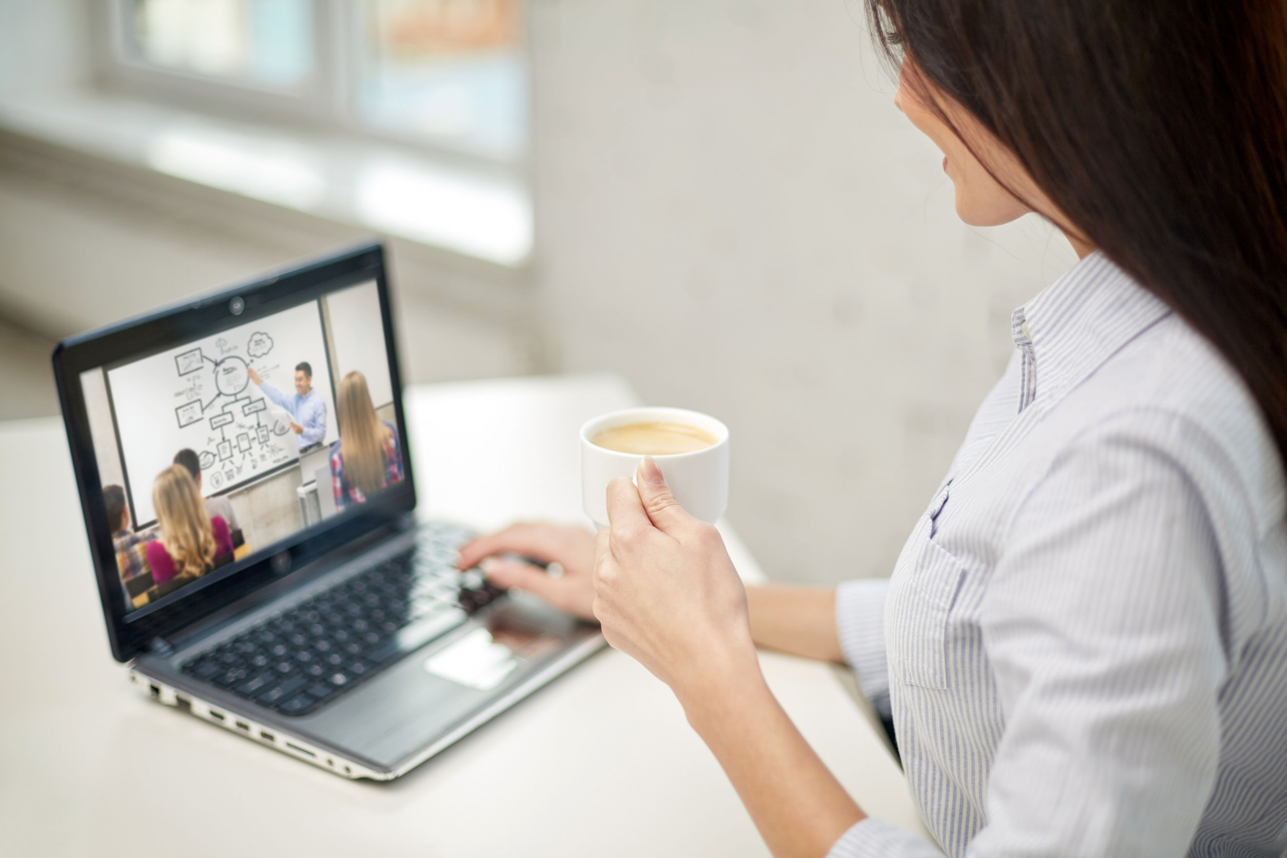 woman with coffee watching webinar on laptop