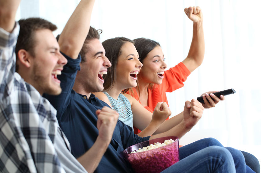 Excited friends watching tv celebrating success