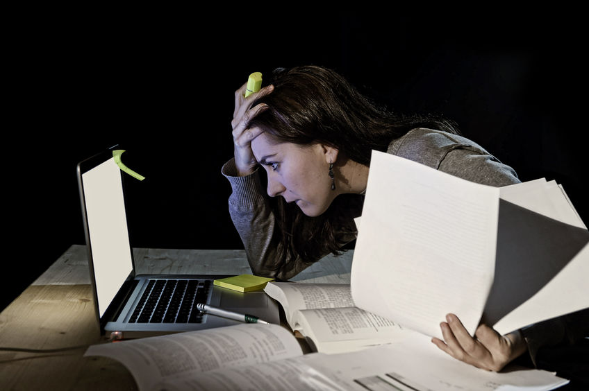 young desperate university student girl in stress for exam studying with books and computer laptop late at night