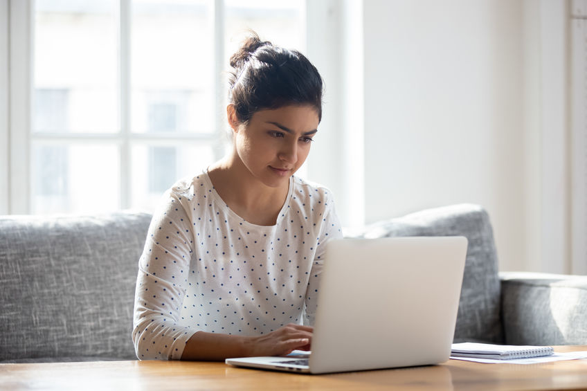 Focused Indian woman using laptop at home, looking at screen