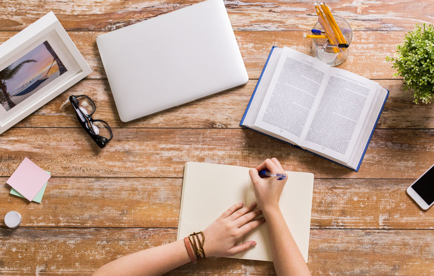 hands with book writing to notebook at table