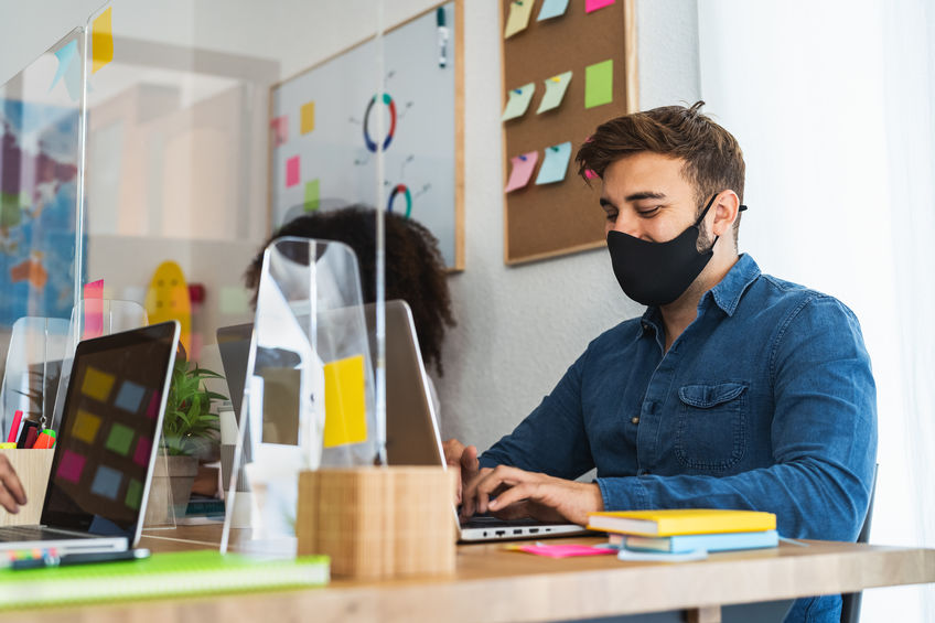 Young people in co-working creative space wearing surgical mask